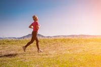 young woman jogging on sunny day at summer mountain