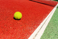Yellow tennis ball on the red cement court to the sun, summer sports.
