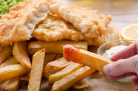 Traditional British street food fish and chips with ketchup sauce and lemon on bakery paper