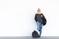 Fashionable young woman standing and waiting against plain white wall on the station whit travel bag by her side.