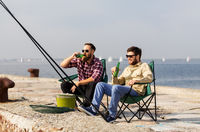 male friends fishing and drinking beer on pier
