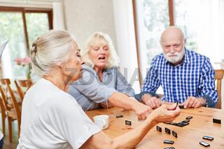 Senioren im Altenheim beim Domino spielen