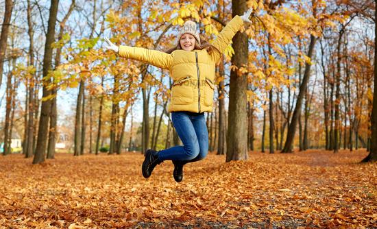 happy girl jumping at autumn park