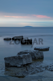 Rocks in silky smooth water after sunset