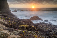 Rugged coastline sunset over Gray Whale Cove State Beach.