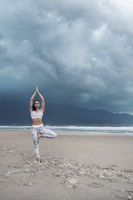 Young sporty slim woman doing yoga exercise on sand of the tropical sea beach with space for text