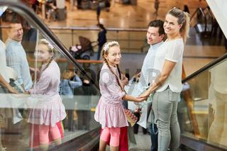 Familie auf Rolltreppe beim Einkaufen