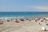 Torrevieja, Spain - June 25, 2019: Holidaymakers enjoy summer vacation beach holidays on seaside near Mediterranean Sea of Cabo Roig sandy coast, sunbath and swim, Torrevieja, Costa Blanca, Spain
