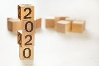 Four wooden cubes arranged in stack with text 2020 on them, space for text image at down right corner