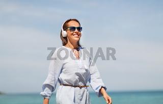 woman with headphones walking along summer beach