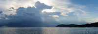 Storm over the sea. Horizontal panoramic view copy space for text on stormy cloudscape blue grey colour horizon over water during sunset, bright colors sunbeams, Asia, Samui Island, Thailand