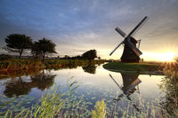 beautiful sunrise over windmill by river