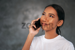 Portrait of beautiful young smiling woman with mobile phone