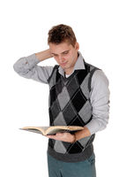 Young man standing reading his book hand on head