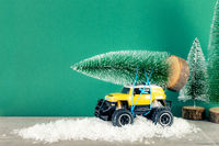 yellow SUV monster car truck toy with fir tree