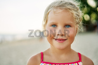 Close up portrait of happy cute little girl. Smiling blonde child on summer