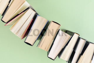 A line of books standing on end running at an angle form one corner of the frame to the opposite corner, on a light green background