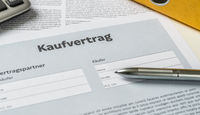 A Purchase agreement with a pen on a desk - Kaufvertrag (German)