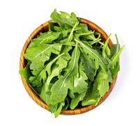 Fresh green arugula leaves on wooden bowl,