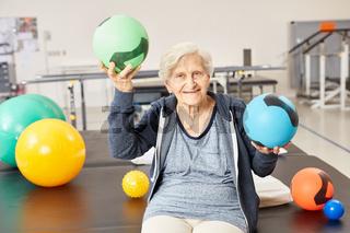Alte Frau balanciert mit zwei Bällen