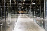 industrial сorridor long illuminated with bright light white floor glass walls