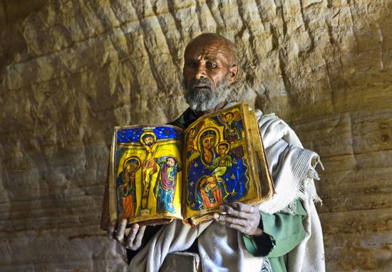 Orthodox priest of the rock church Mikael Mellehayzengi shows liturgical book, Tigray, Ethiopia
