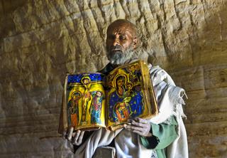 Orthodoxer Priester der Felsenkirche Mikael Mellehayzengi zeigt liturgisches Buch,Tigray,Äthiopien