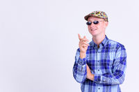 Happy young hipster man with sunglasses thinking