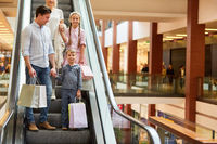 Familie auf Rolltreppe im Shoppingcenter