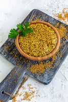 Bowl with grain mustard and yellow mustard seeds.