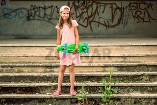Girl with skateboard at abandoned building