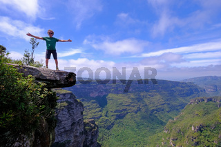 The cliffs of the Cachoeira Da Fumaca, Smoke Waterfall, with a hiker standing on the edge, Vale Do Capao, Bahia, Brazil