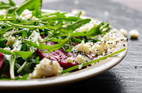 Clay dish with beetroot arugula and feta cheese salad on slate stone tray closeup view