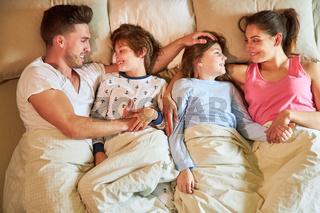 Eltern und Kinder kuscheln im Bett