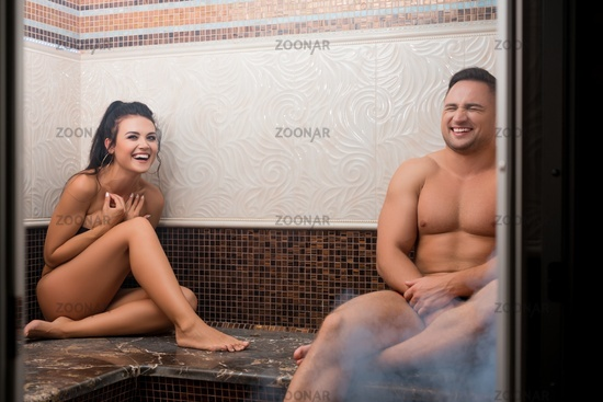 Young happy couple relaxing in sauna