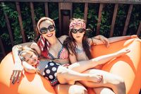 Beautiful mother with two daughters sitting on an orange lounge