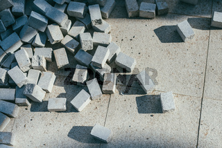Abstract background of modern cobblestone pavement close-up. Underconstruction renovation concept. Pile of bricks lit by sun