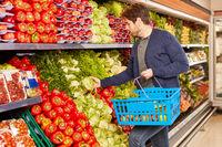Mann mit Einkaufskorb in der Gemüseabteilung