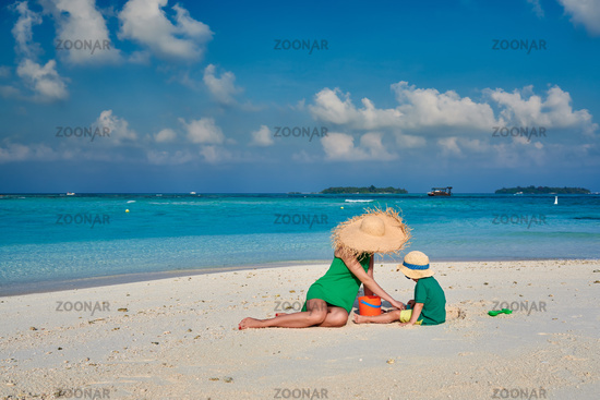 Woman in green dress with three year old boy on beach