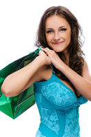 smiling beautiful woman with dark hair in blue dress with green bag