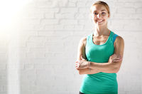 Portrait of happy smiling caucasian young sports woman against white brick wall. Place for text.