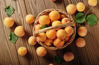 Top view of Wicker basket with ripe apricots on wooden table