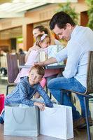 Junge sucht neugierig in Einkaufstüten