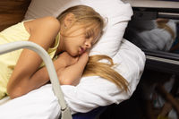The girl fell fast asleep on the top shelf of a reserved seat car