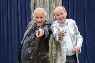 Two older men giving a lively stage performance