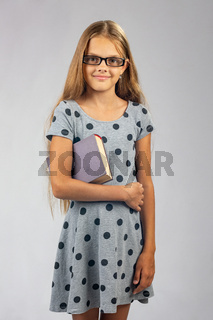Schoolgirl in glasses with a book in her hands