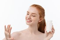Portrait of good-looking young caucasian woman holding pills, trying to take care of immune system and health over gray background.