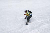 Snowboarder downhill on snowy ski slope