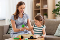 pregnant mother and daughter with toy blocks
