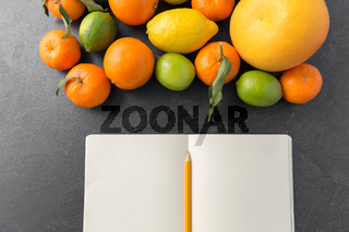 close up of fruits and notebook on slate table top